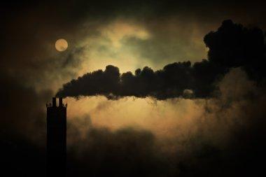 Sun shines through smoke from factory chimneys, telephoto shot.