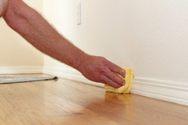 Male caucasian hand and arm seen wiping a folded yellow rag along the lower white wall trim near the wood floor to remove dust. stock vector