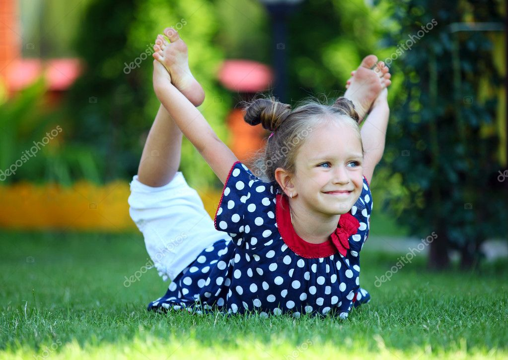 Cute four-year old girl exercising outdoors