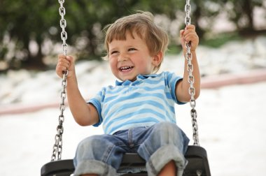 Little boy having fun on chain swing