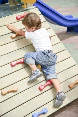 Little boy climb in playground.