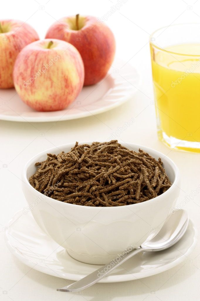 Healthy breakfast with fresh apple, orange juice and wheat bran cereal