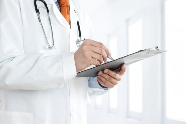 Doctor at the hospital hallway writing notes on the clipboard stock vector