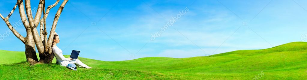 Pretty woman sitting with laptop under tree. Beautiful panoramic