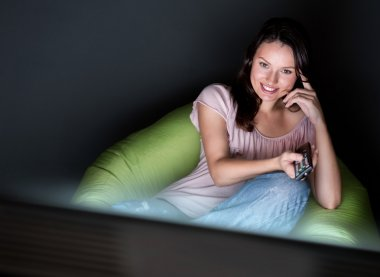Young woman watching TV sitting on the beanbag at home