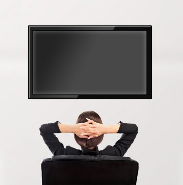 Woman watching tv. Photo from behind. Editable copyspace at the