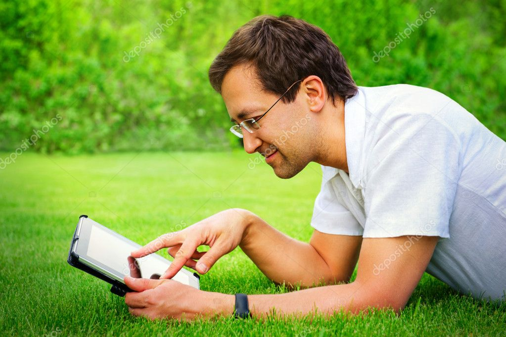 Adult man working with tablet computer outdoor in park