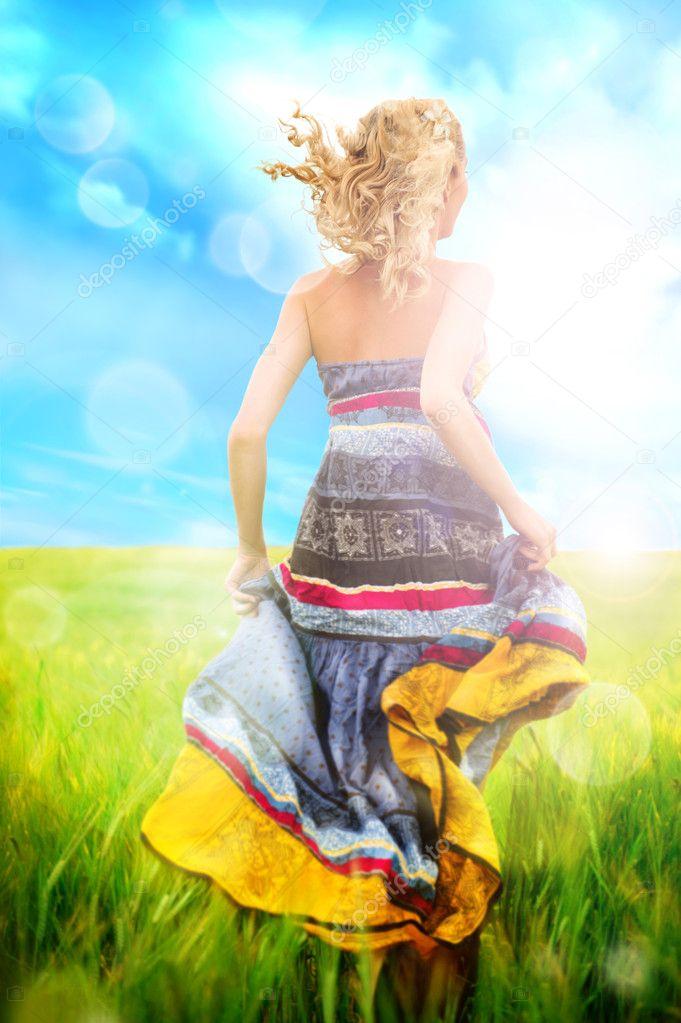 Portrait of romantic woman running across field wearing bright e