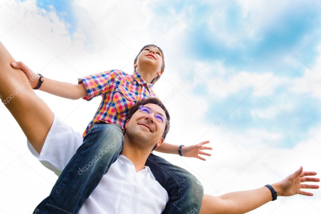 Portrait of smiling father giving his son piggyback ride outdoors against sky stock vector