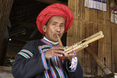 Photo Thailand, Chiang Mai, Karen Long Neck hill tribe village (Kayan Lahwi), Karen man in traditional costumes playing a flute