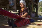 Photo Thailand, Chiang Mai, Karen Long Neck hill tribe village (Kayan Lahwi), a Karen woman in traditional costumes is making a carpet