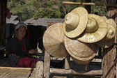 Photo Thailand, Chiang Mai, Karen Long Neck hill tribe village (Kayan Lahwi), a Karen woman in traditional costumes and oriental hats for sale