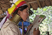 Photo Thailand, Chiang Mai, Karen Long Neck hill tribe village (Baan Tong Lhoung), Long Neck woman in traditional costumes reading a magazine. Women put brass rings on their neck when they are 5 or 6 years