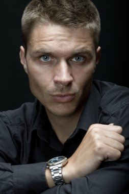 Handsome man with watch on his hand on the black background