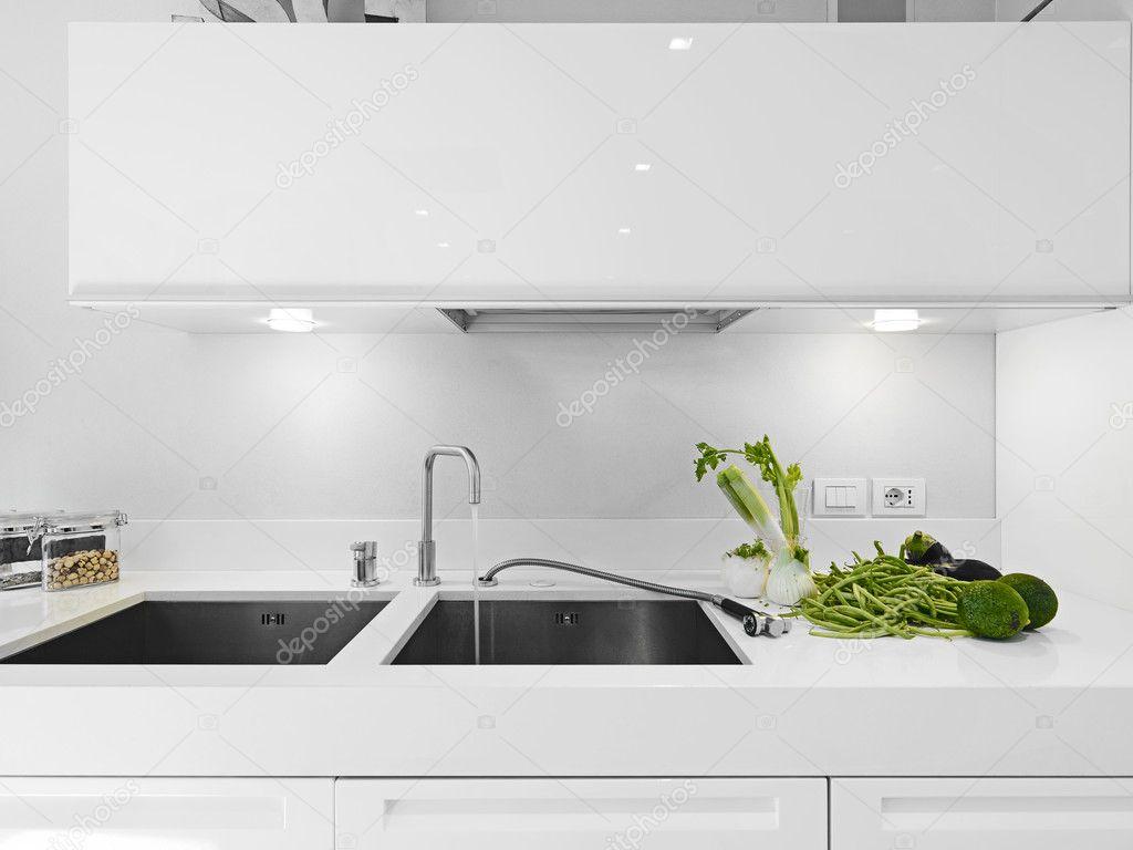 Groenten in de buurt van de kraan in de moderne witte keuken