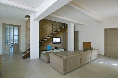 Modern living room with staircase and concrete floor