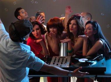 Women flirting with dj in night club