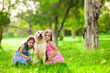 Two young girls hugging golden retriever dog