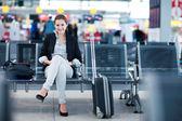 mladá žena cestující na letišti, pomocí její tabletový počítač