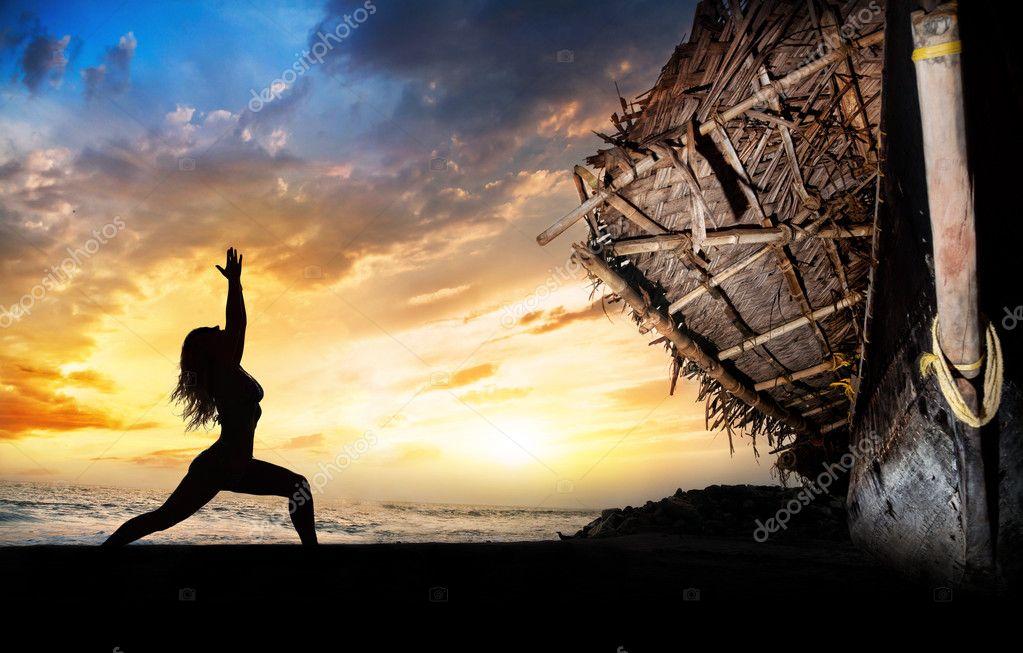 Yoga silhouette warrior pose near boat