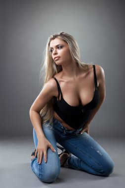 Sexy young woman posing in black and jeans