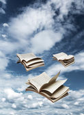 Fotografia tre libri di volare sul cielo blu