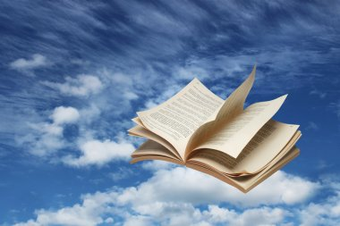 Open book flying on blue sky