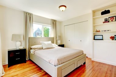 White bedroom with hardwood cherry floor.