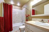 Fotografie elegantní béžová a červená koupelna s vanou a umyvadlem