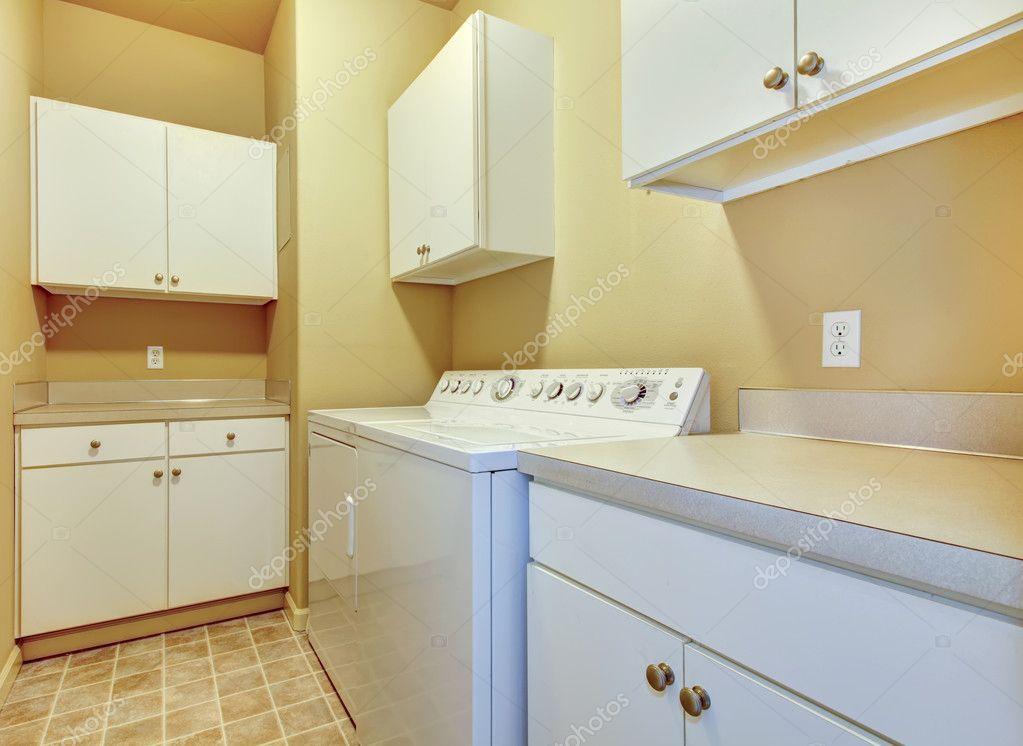 Pareti Bianche E Beige : Lavanderia con armadi bianchi e pareti gialle u foto stock