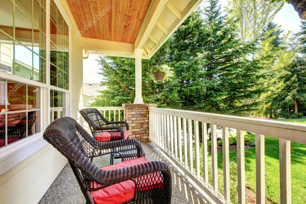 Front porch with brown chairs and red cushions.