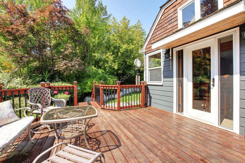 exterior de la casa con gran terraza abierta con muebles de exterior ...