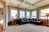 Living room wih many large windows and blue sofa.