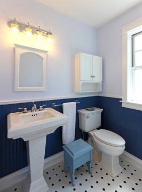 Bathroom with sink and toilet with blue walls.