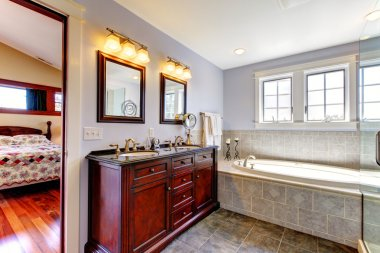 Nice lavendar bathroom with tub and wood cabinet with two sinks.