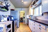 Bílá kuchyně s šedými zdmi a hrnce a pera