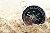 Compass on the sea sand and place for text