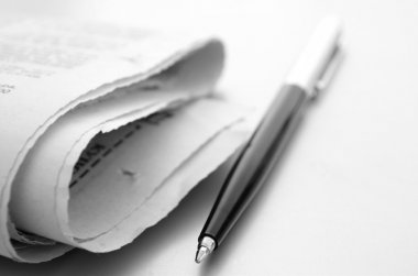 The newspaper and ball pen on a table