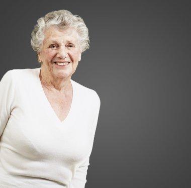Pretty senior woman smiling against a black background
