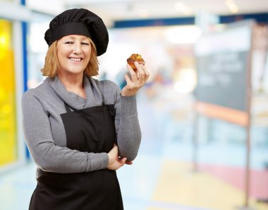 Portrait of middle aged cook woman holding a homemade muffin ind