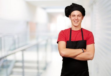 Portrait of young cook man wearing uniform and smiling against a