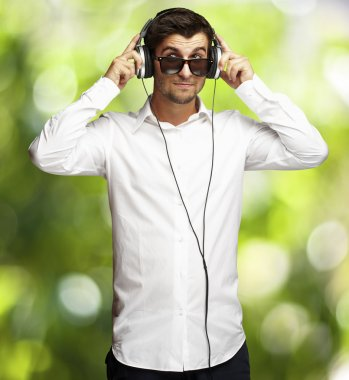 Portrait of young man listening to music using headphones agains