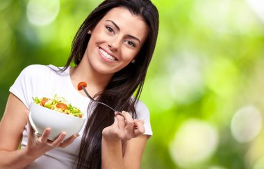 Portrait of healthy woman eating salad against a nature backgrou
