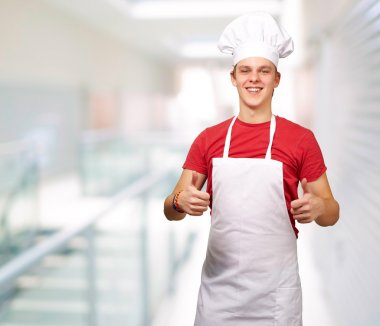 Portrait of young cook man doing success symbol at entrance of m