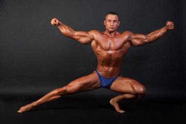 Bodybuilder posing on dark background.