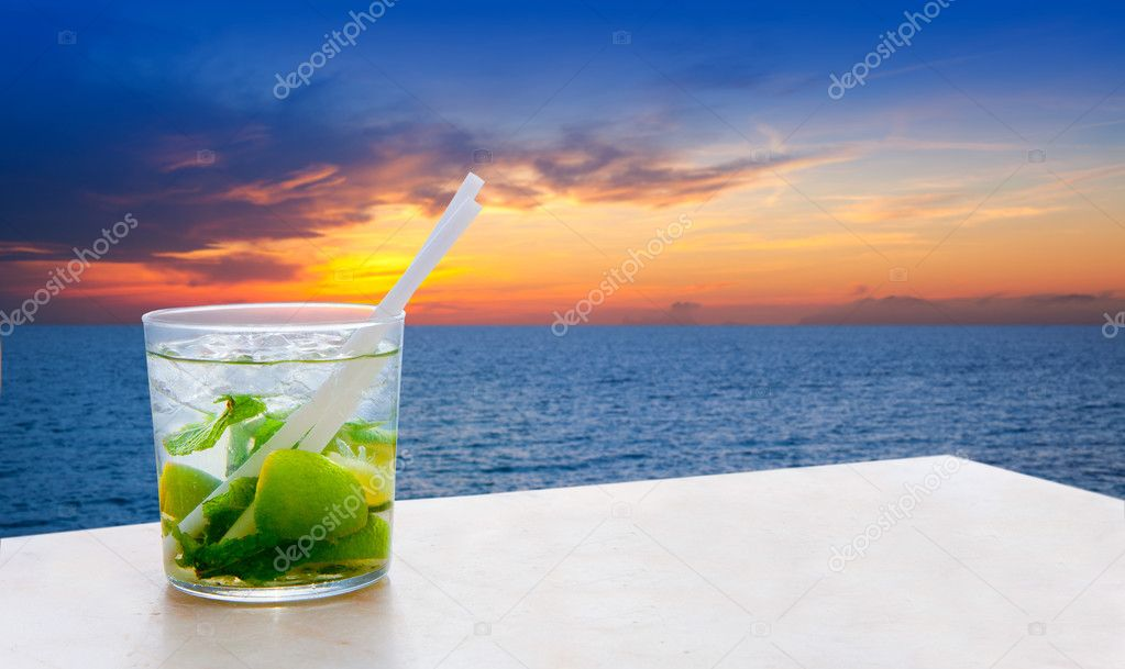 Mojito cocktail on a sunset beach golden sky
