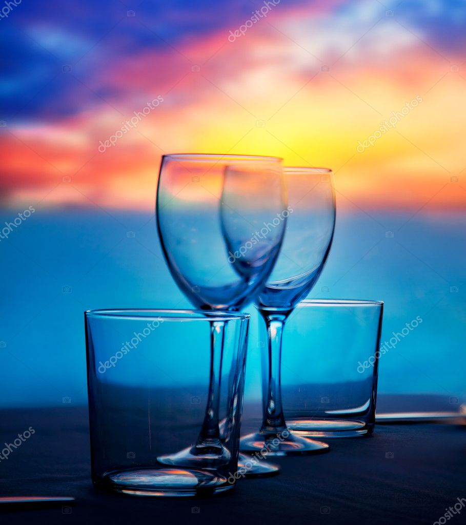 Dish of cups and crystal glasses on sea sunset