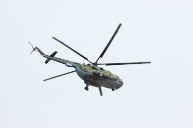 Russian flying military helicopter MI-8 make virage in cloudy sky