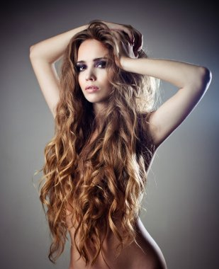 Sexy young woman with beautiful long curly hair