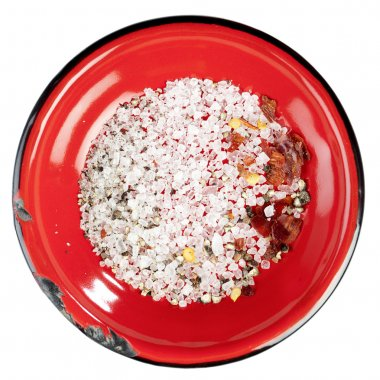 Seasoned sea salt in enamel red plate, isolated